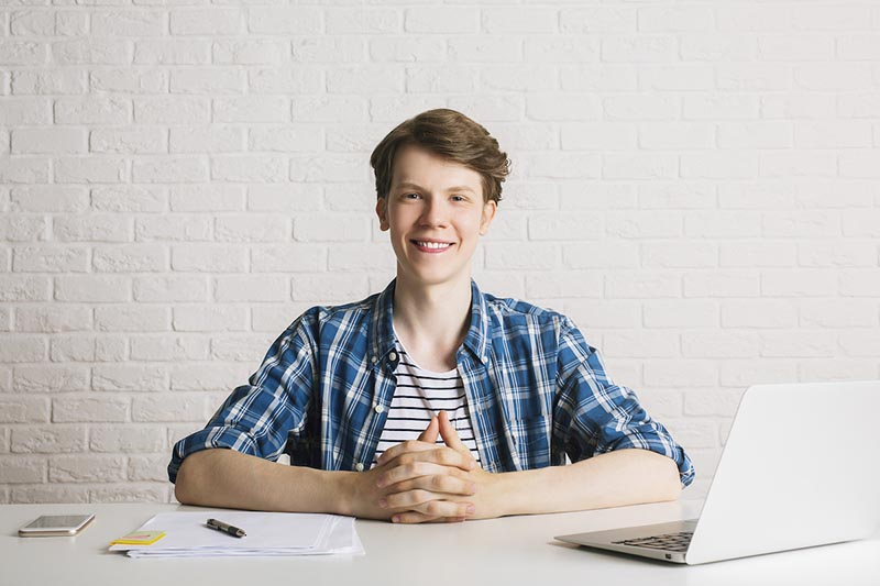 Smiling male student at desk